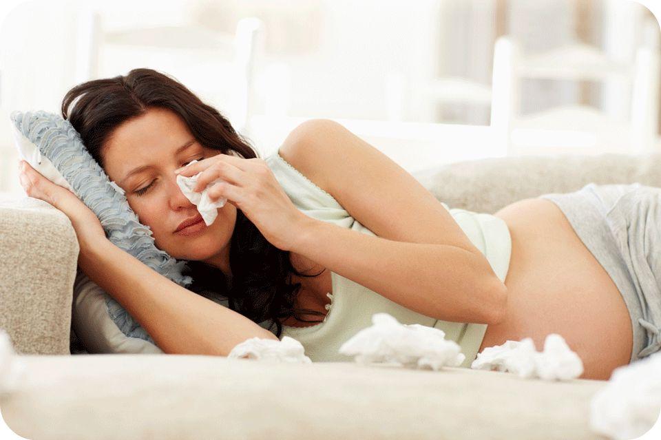 Беременная девушка лежит и вытирает нос салфеткой