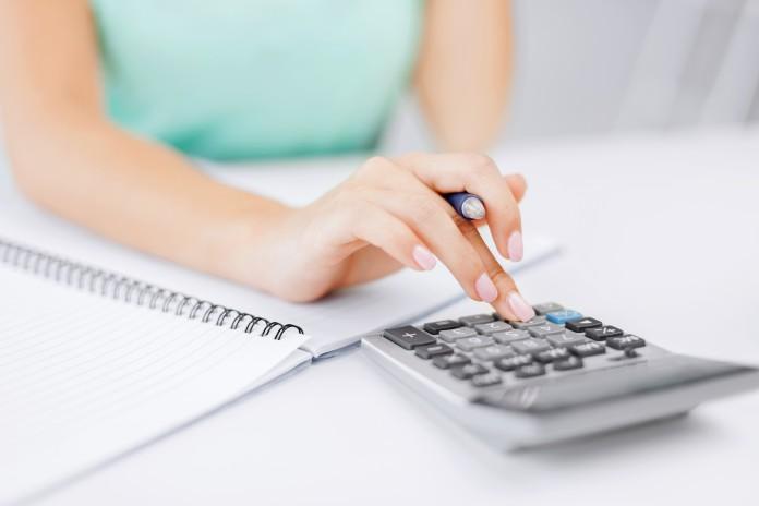Девушка проводит расчеты на калькуляторе