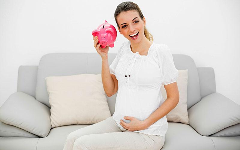 Беременная женщина держит в руке копилку