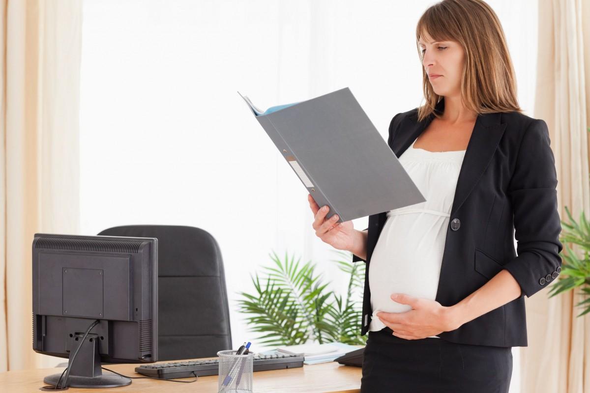 Беременная женщина читает документы