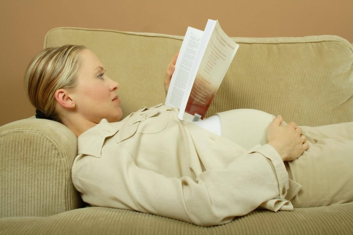 Беременная женщина лежит на диване и читает книгу