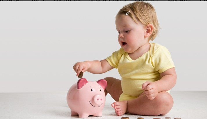 Маленькая девочка кладет деньги в копилку