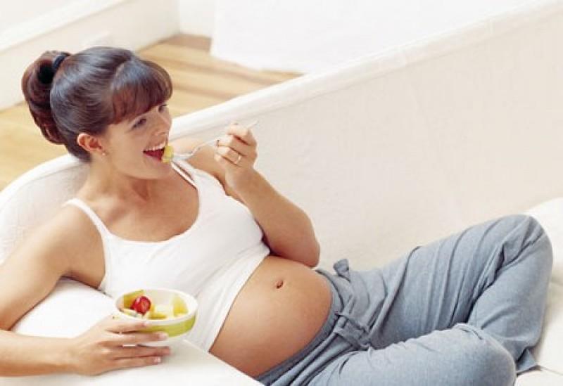 Беременная женщина кушает салат