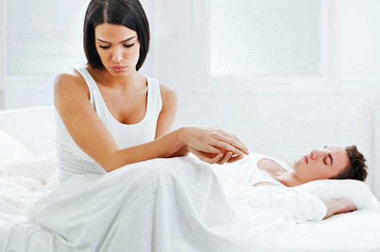 Женщина сидит на постели со своим мужчиной