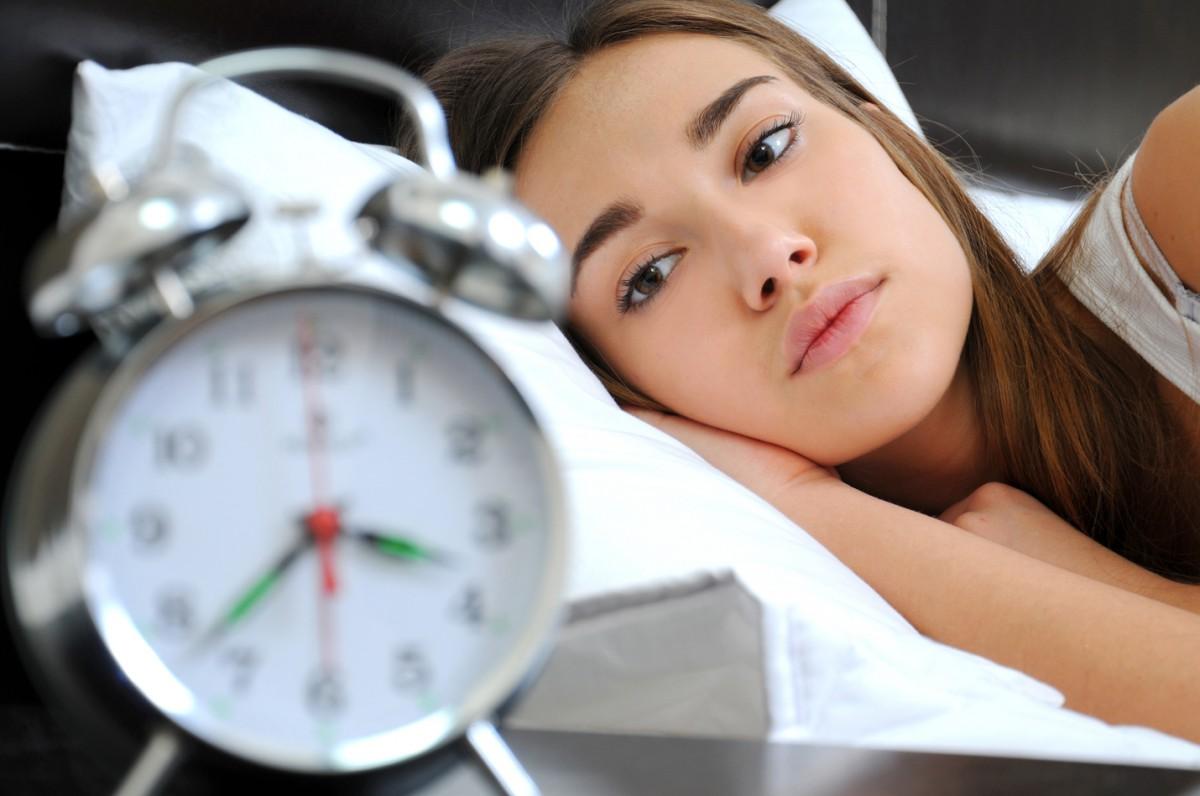Девушка лежит и смотрит на часы