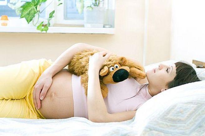 Беременная девушка держит мягкую игрушку