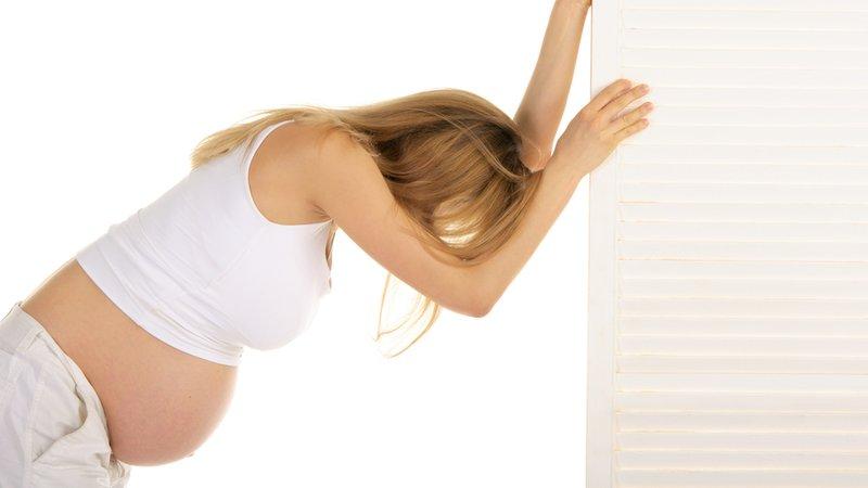 беременная женщина наклонилась к стенке