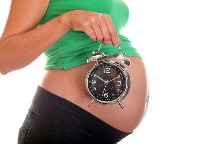 часы в руках у беременной