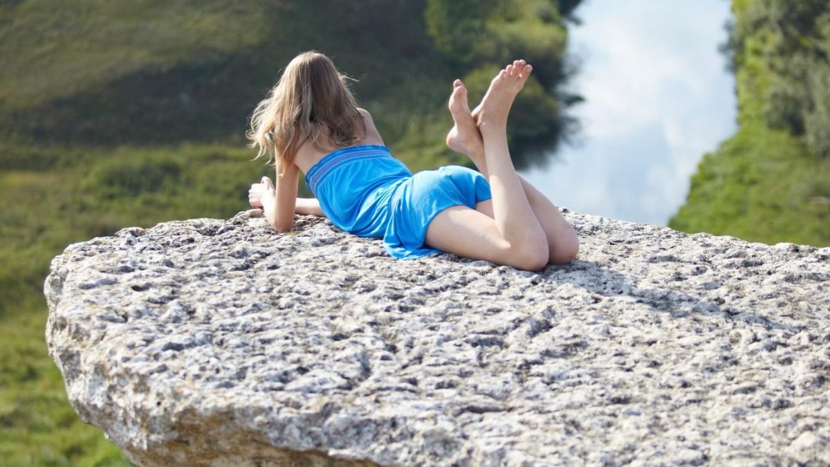 девушка в синем на камне