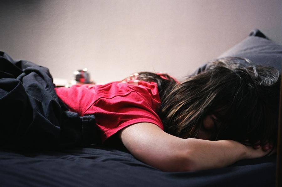 Девушка лежит на черном постельном