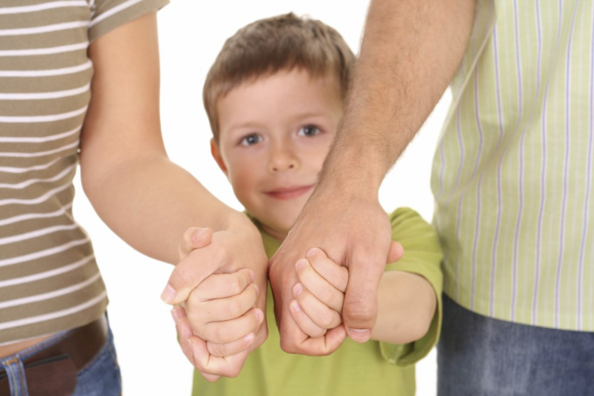 Мальчик держит родителей за руки