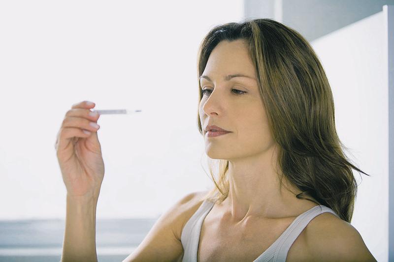 Женщина смотрит на градусник