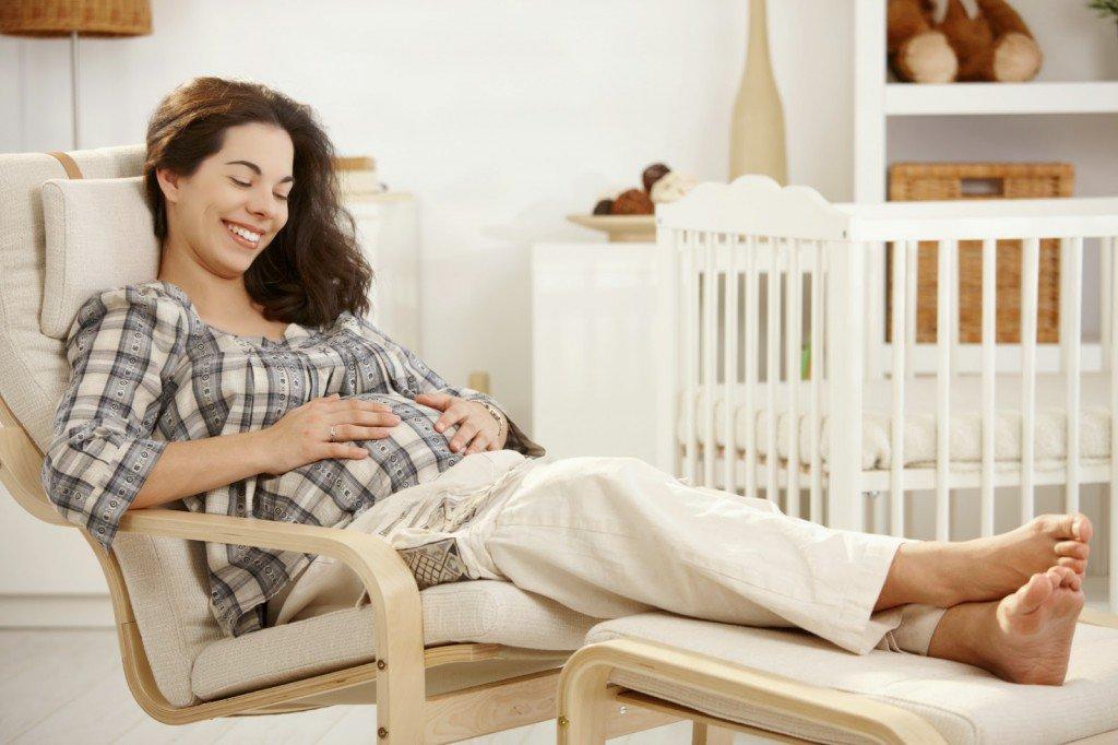 Беременная женщина сидит в кресле