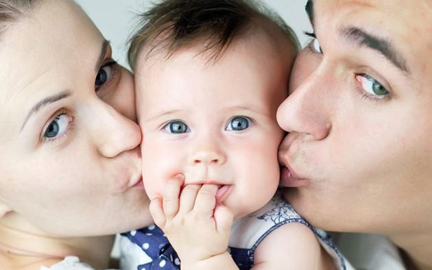 Мама и папа целуют сына