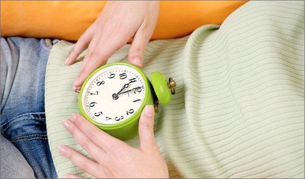 Девушка держит часы на животе