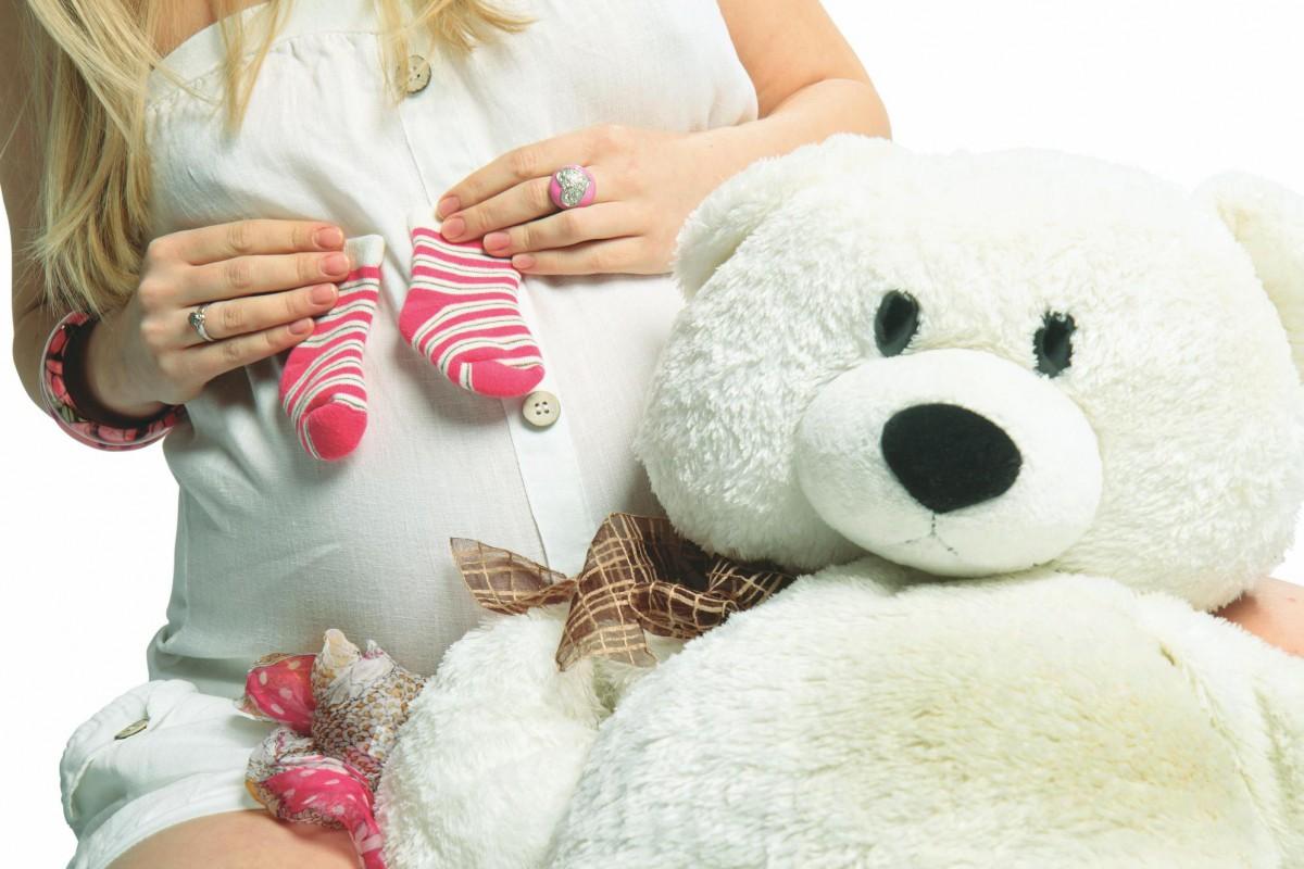 Беременная женщина держит в руках носочки