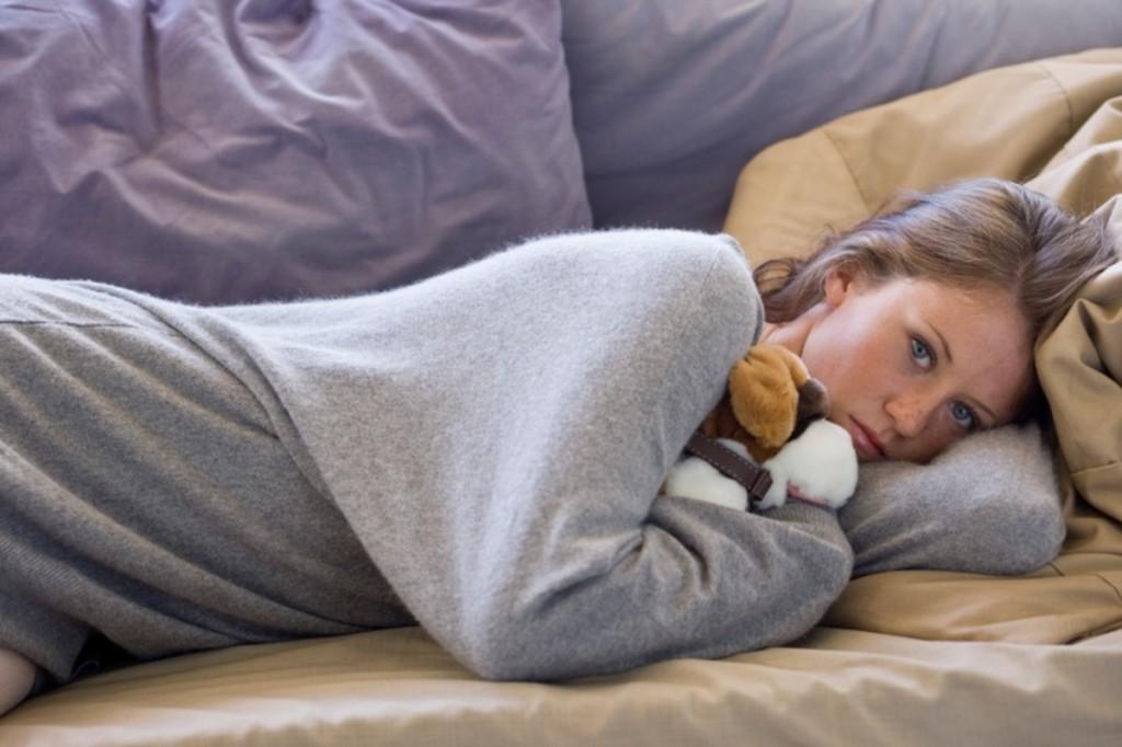 Девушка лежит в кровати с игрушкой